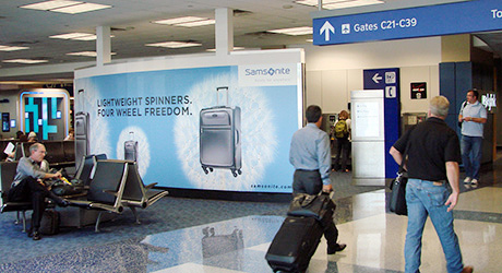 A large wall wrap advertising luggage within an airport.